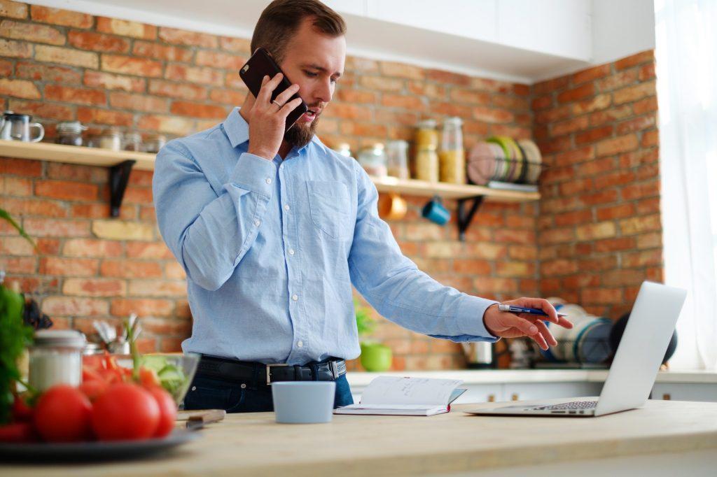 Homem no telefone e na internet para atualizar boleto bancoob